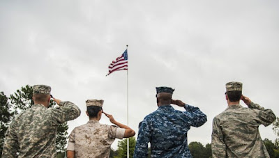 US military personnel saluting the flag