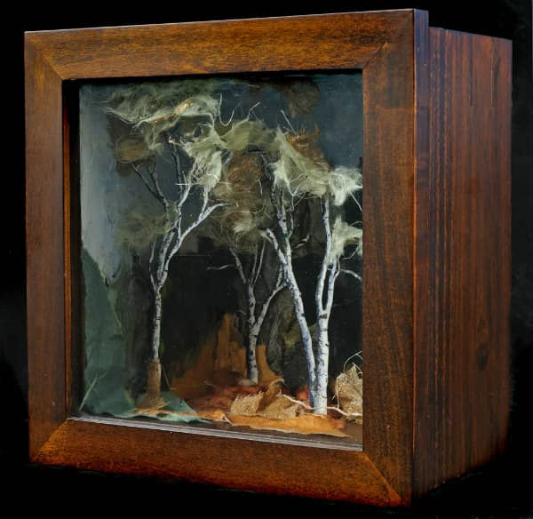 square wooden box containing textured paper collage of dimensional tree scene