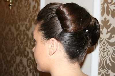 Wedding hair featuring a hair bow and sleek updo