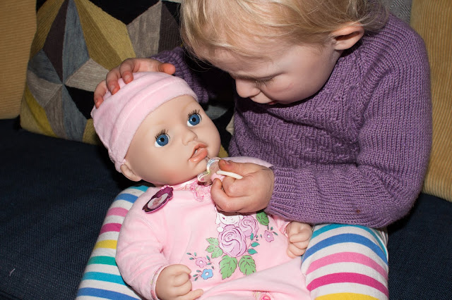 A toddler holding the dolls head while putting Baby Annabell's dummy in