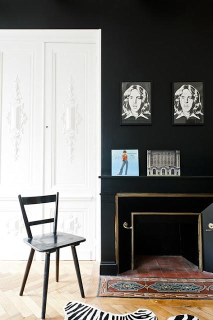 porte blanche avec moulures et murs noirs dans appartement ancien