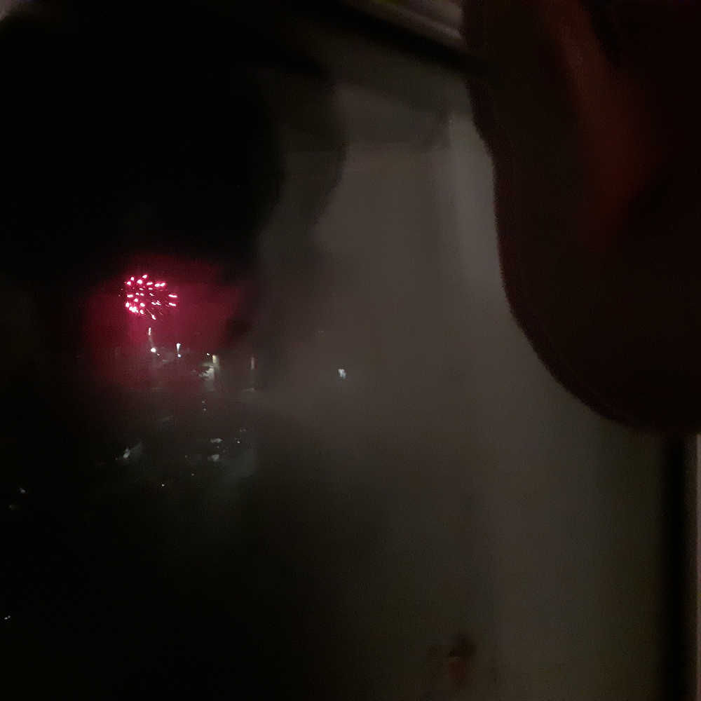 Fireworks and toddler's reflection through a window