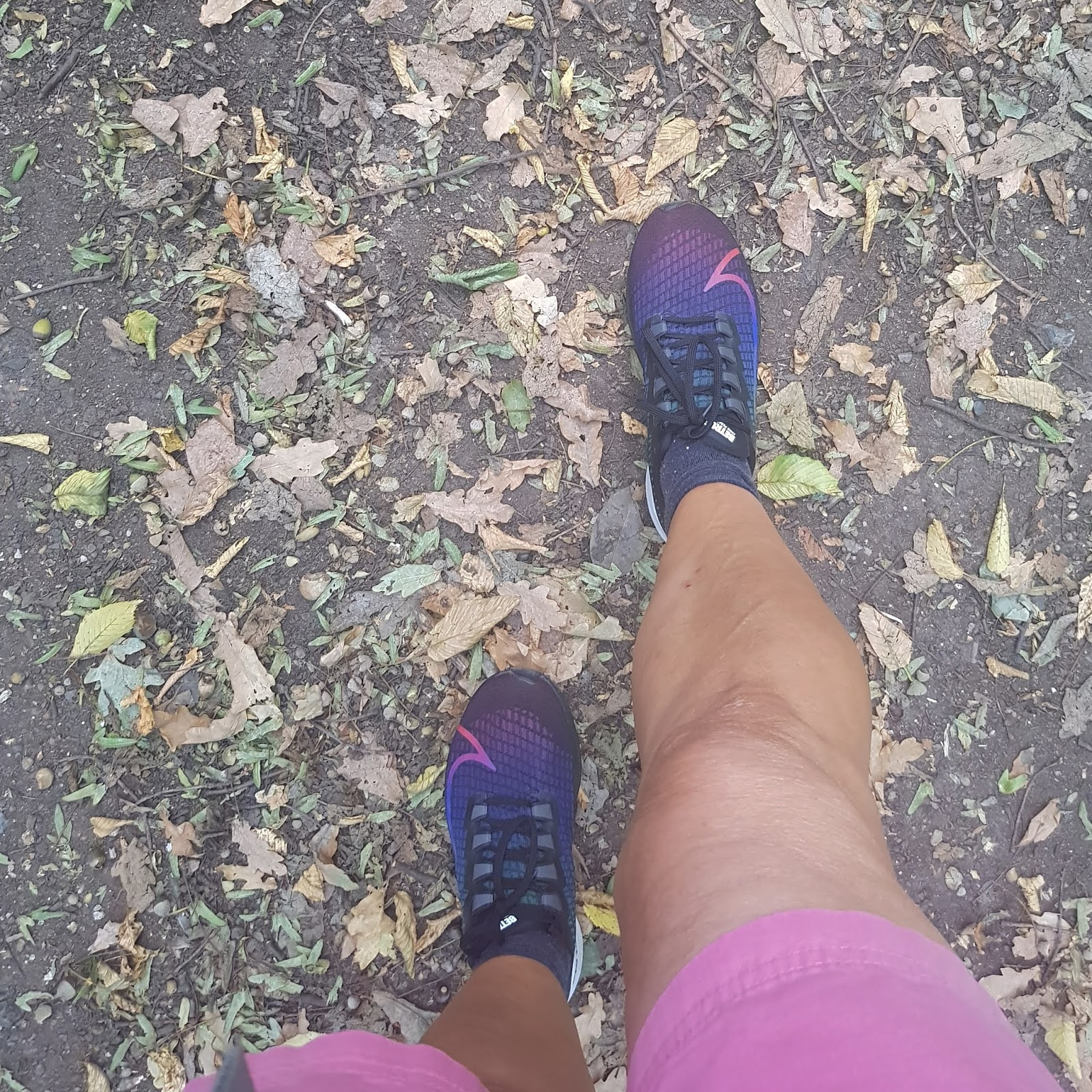 Blogger Gail Hanlon strides out on a walk through autumnal leaves wearing Nike Be True Air Zoom Pegasus trainers