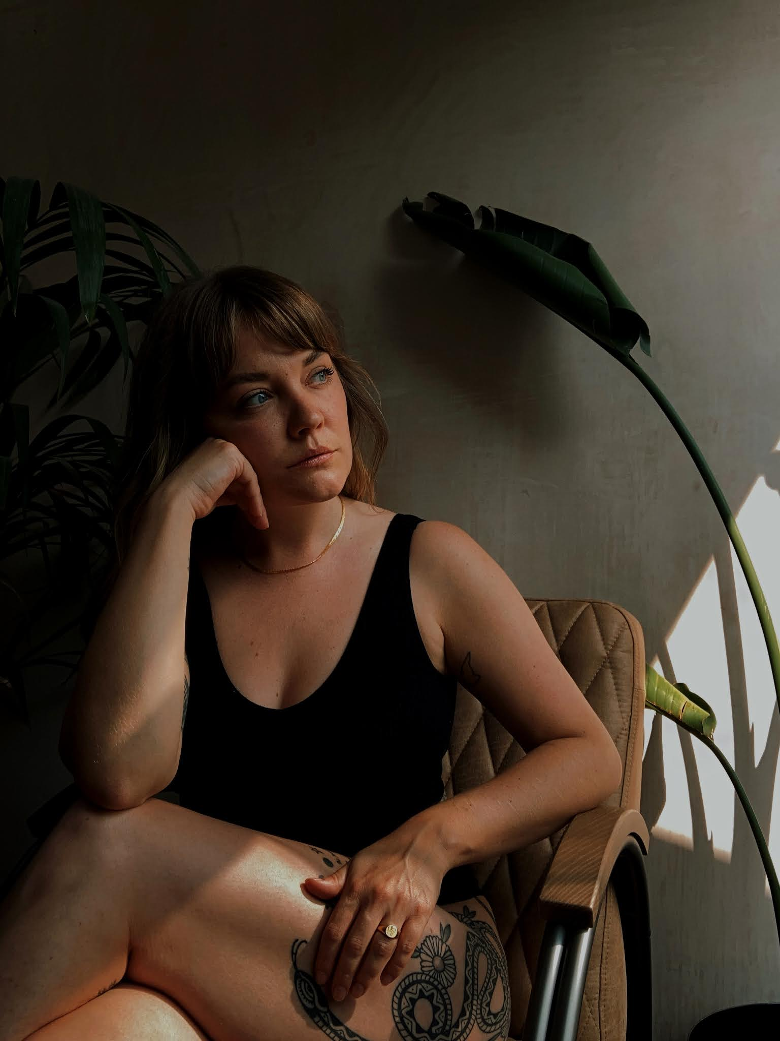 Lyzi sitting on a vintage chair in front of a plaster wall and large plants. Wearing simple black underwear and a Daisy x Estee Lalonde snake chain and forget me not signet ring.