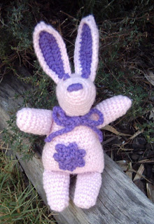 "The same toy design as ""Richard Rabbit"" except in pink with dark purple inner ears and nose.  This rabbit has a dark purple flower applique on its body and a purple crocheted ribbon around its neck tied in a bow. It is sitting on the edge of the garden bed."