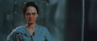 Angela Bettis as Mandy, in scrubs with blood on her face
