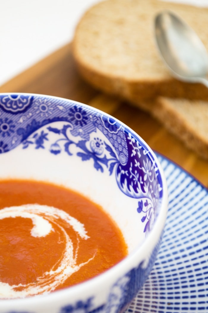 A bowl of tomato soup next to slices of brown bread