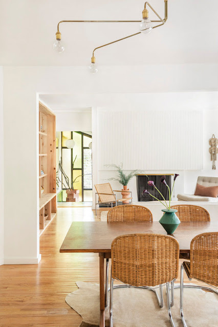 neutral living and dining room with rattan chairs and thin wood paneling above fireplace