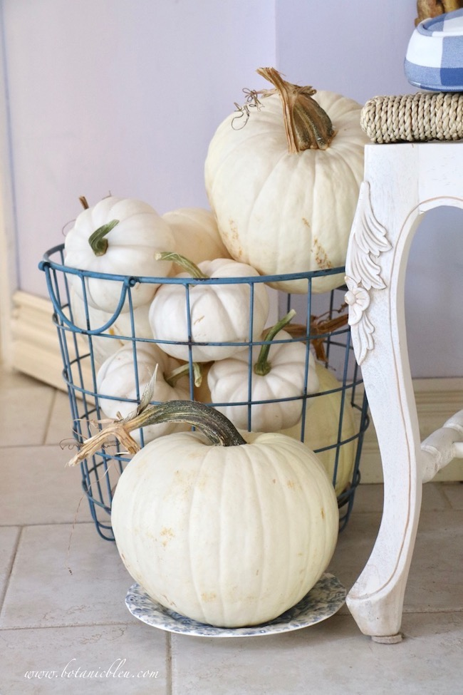 Fall blue and white cottage style small foyer lives large with blue metal wire basket filled with white pumpkins