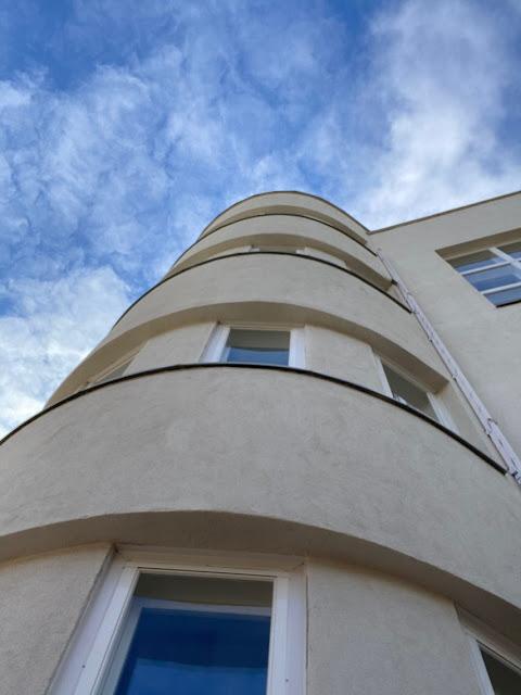 Rakennuksen pyöreä tornimainen kulma. Kuvattu alhaalta ylös, taustalla näkyy taivasta.