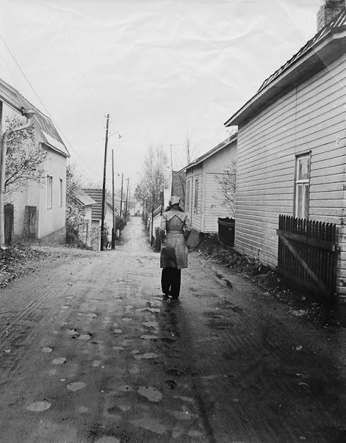 mustavalkoisessa kuvassa nainen kävelee kuvaajasta poispäin pitkin  kapeaa hiekkatietä, jota reunustavat vanhat puutalot.