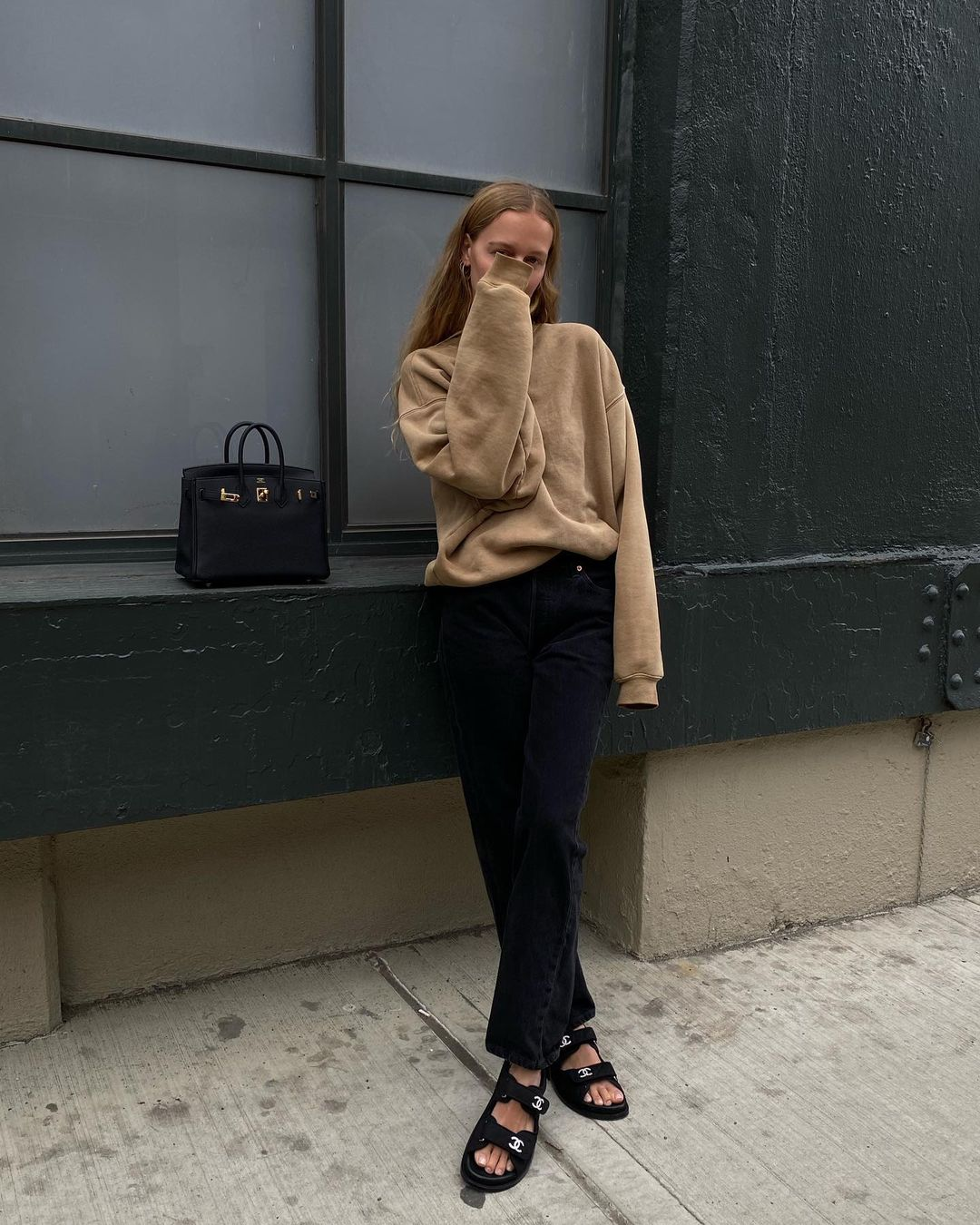 25 Basic Yet Cool Sweatshirts to Shop Now — Instagram outfit idea — @mvb Marie von Behrens in a tan sweatshirt, an Hermès bag, black jeans, and Chanel dad sandals