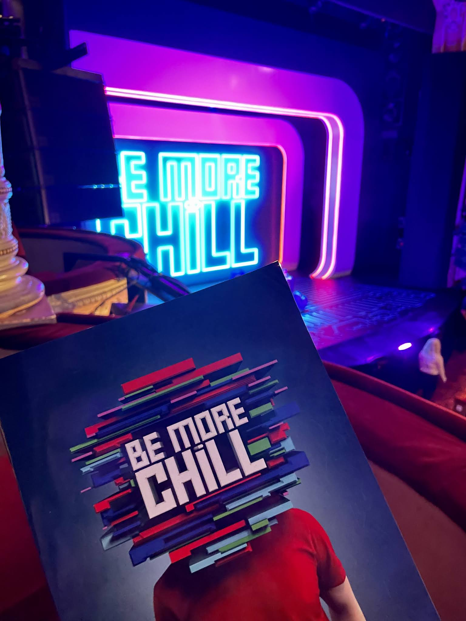 The programme for Be More Chill the musical is being held up in front of the stage.