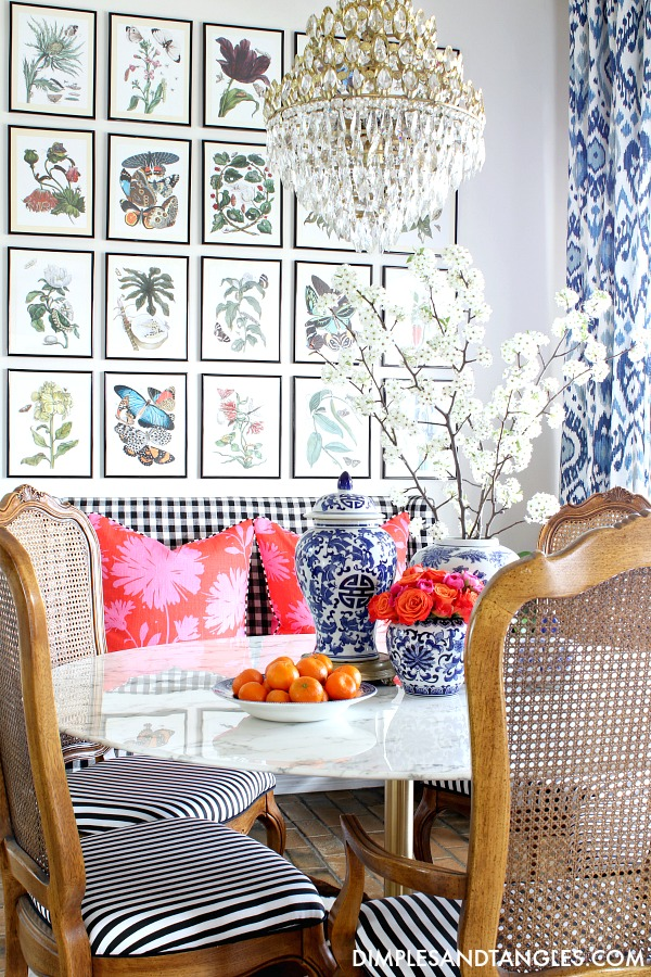botanical gallery wall, vintage crystal chandelier, blue and white curtains, cane back chairs, black and white chair