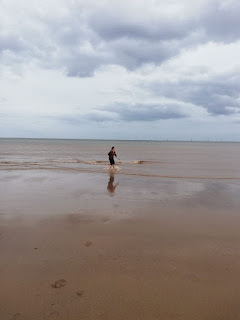 a woman wades in the surf on a sandy seashore