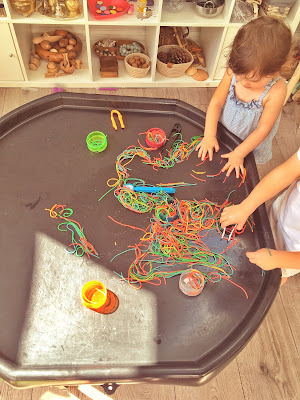 rainbow spaghetti and tweezers on a tuff tray