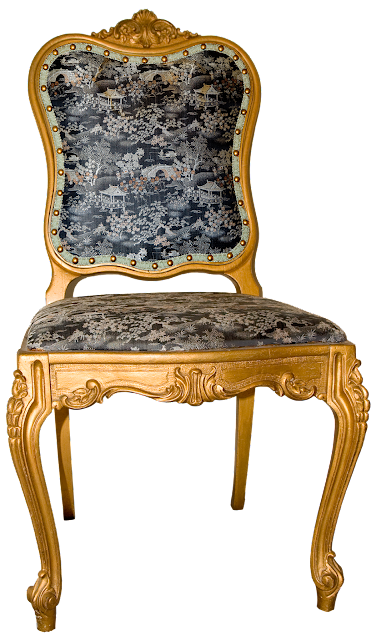 A gold painted, and intricately carved Victorian chair covered in a reproduction Oriental pictoral silk fabric.