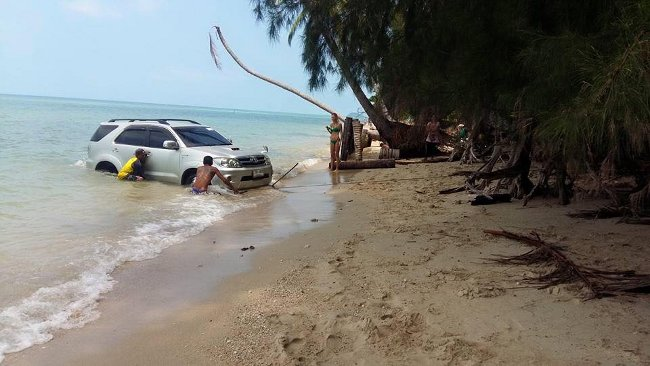 тайцы вытягивают автомобиль из моря