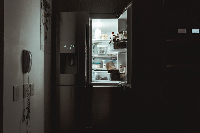 Darkened kitchen with the fridge door open