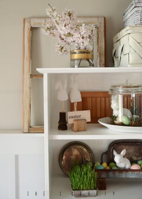 Wheat grass in Spring vignette in white book shelf.