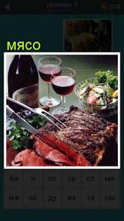 приготовлено мясо от которого отрезают кусочек ножом и вилкой