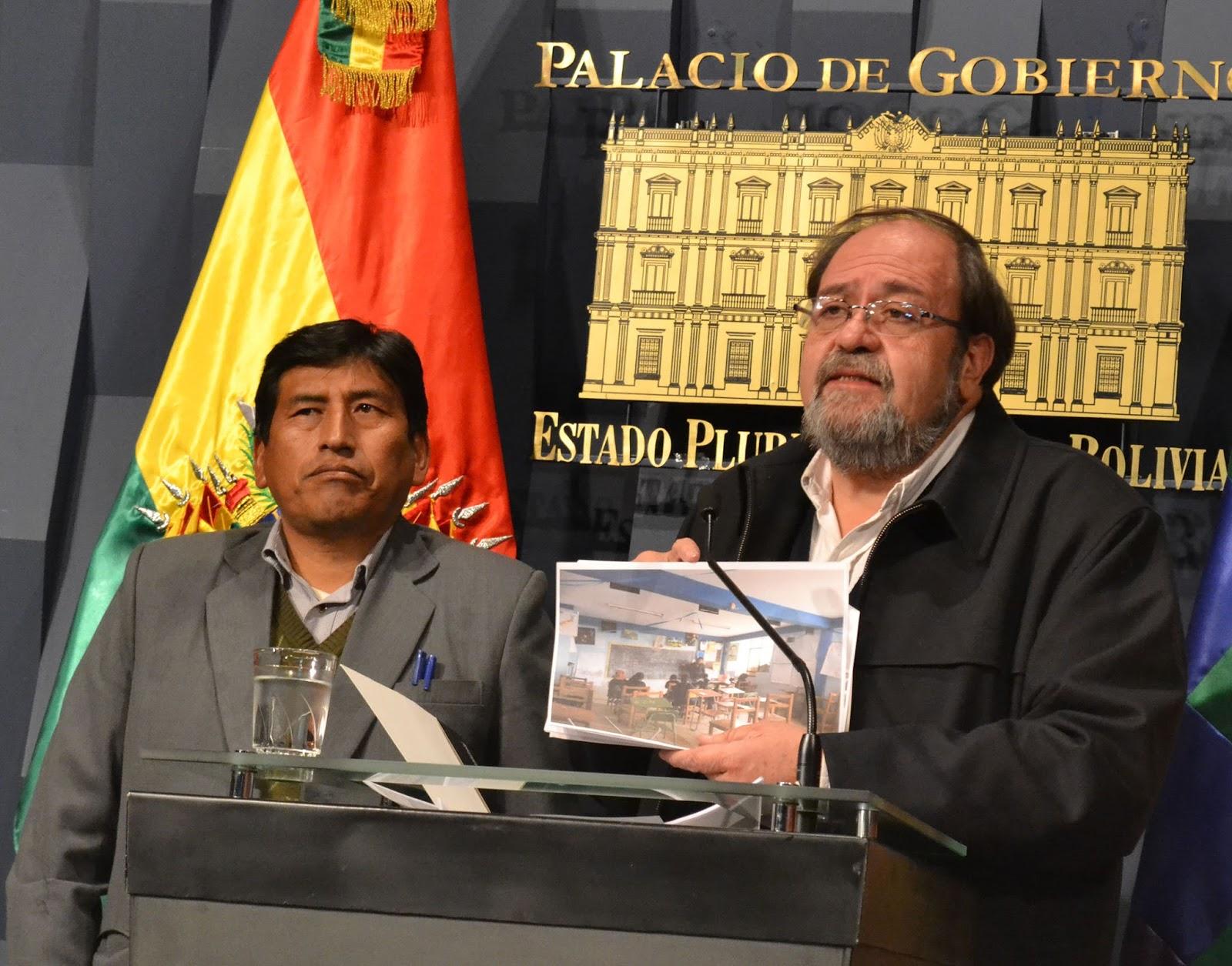 Ministro Aguilar en conferencia de prensa con fotos de escuelas en Achacachi