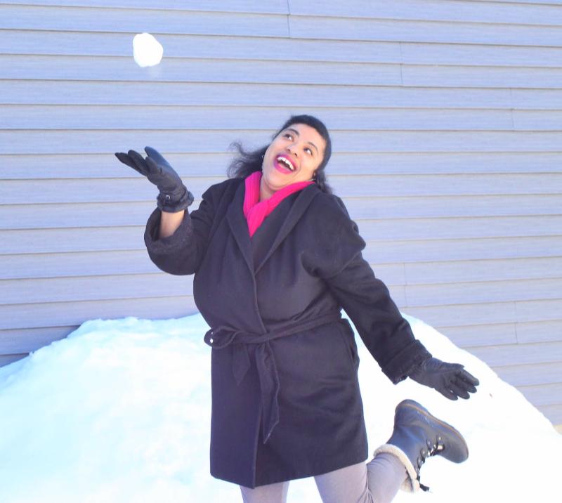 a black woman throwing a snowball in the air