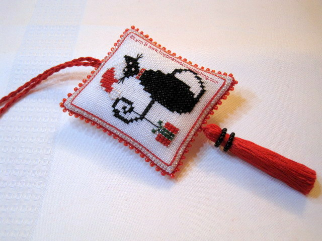 Cute Christmas Mini Black Cat cross stitch finished into a beaded scissor fob, the cat is wearing a red and white santa hat with a parcel hanging from his tail