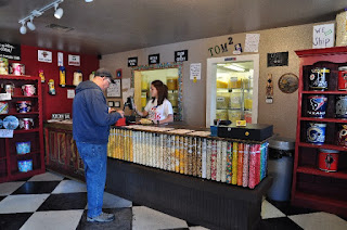 Man buying flavored popcorn from lady at counter