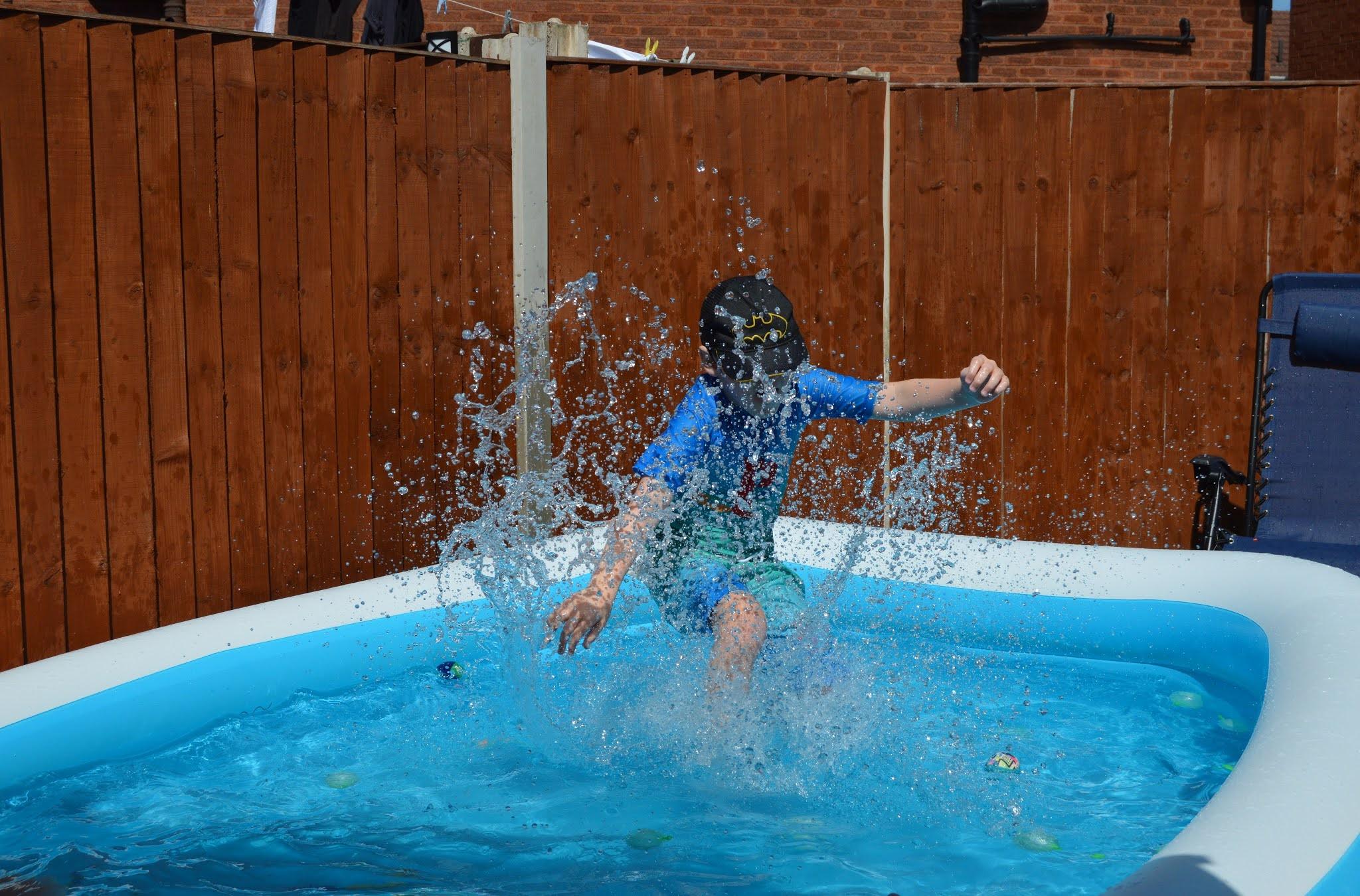 boy splashing in the pool