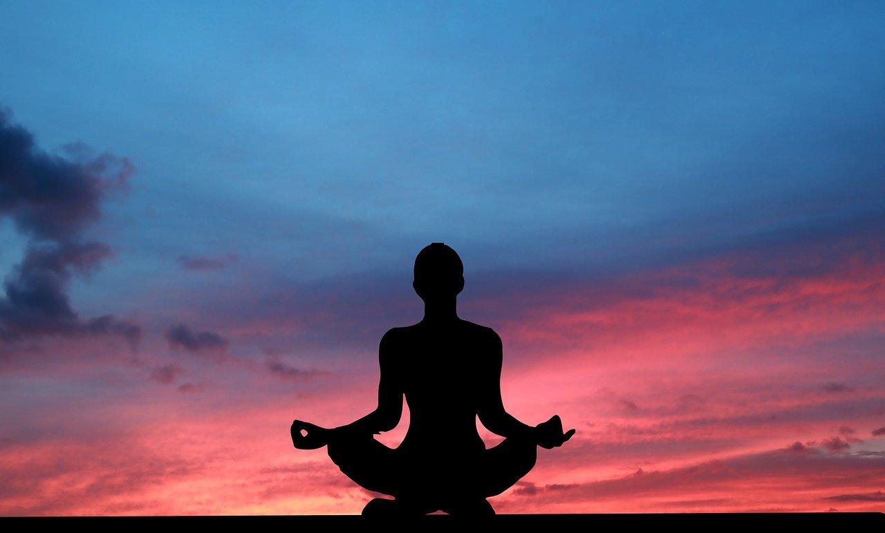 silhueta de mulher meditando no por do sol