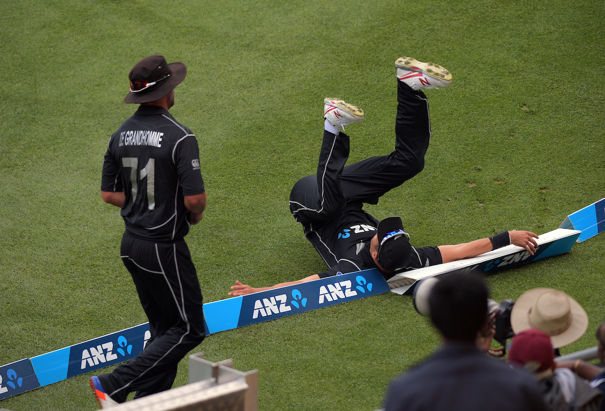 Trent Boult falls over the boundary ropes