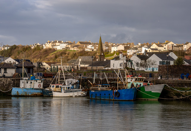 Photo of fishing boats in the harbour with Christ Church, Maryport, in the background