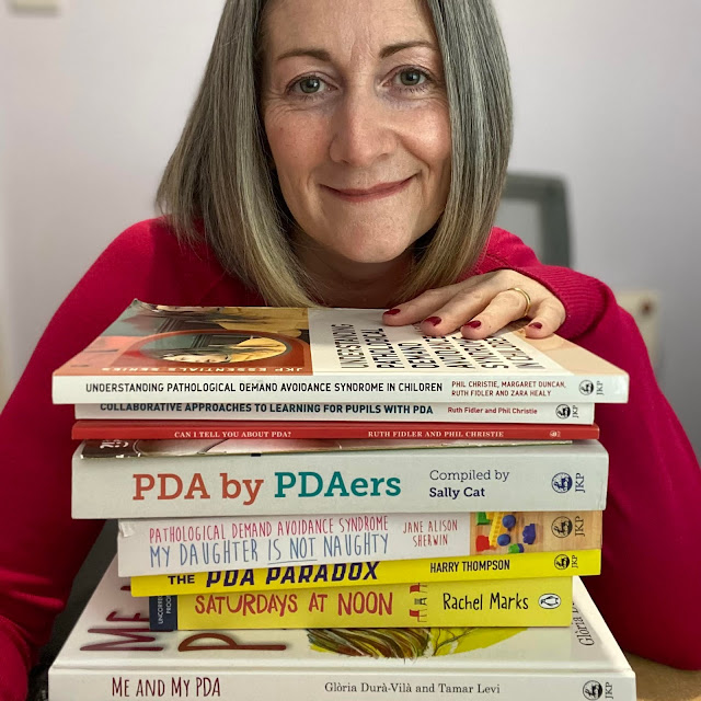 Face shot of Steph, a 40 something mum with grey hair, smiling at the camera as she peers over the top of a pile of books about PDA