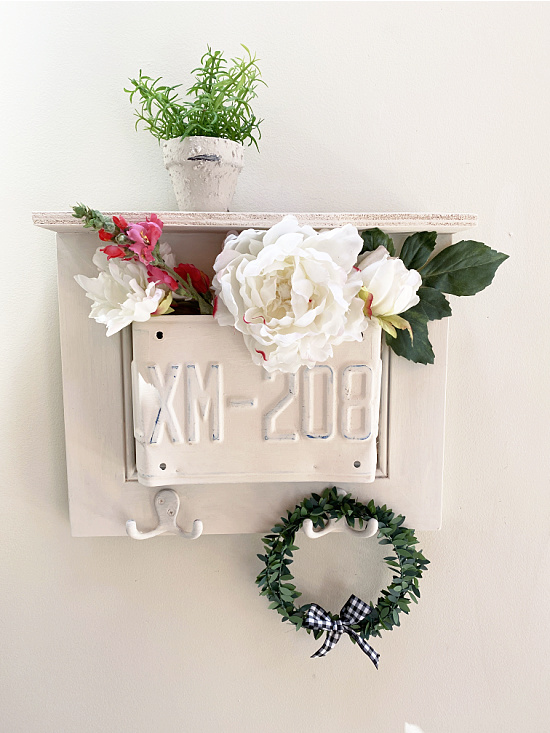 white shelf with plant and wreath filled with flowers