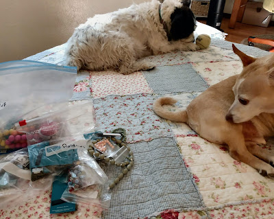 two dogs on the bed waiting for the rosary-making to begin