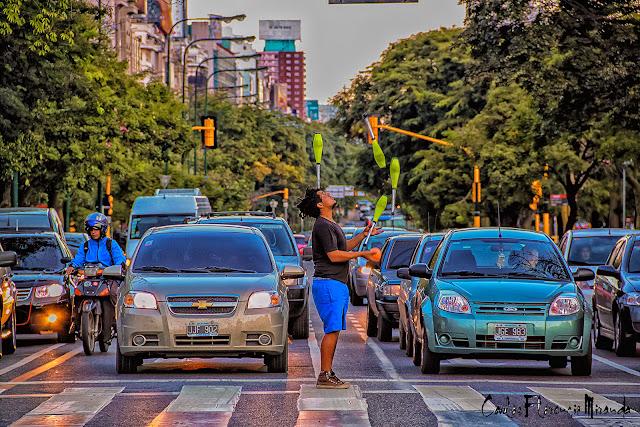 En un corte del semáforo hombre haciendo malabares ante los autos detenidos.