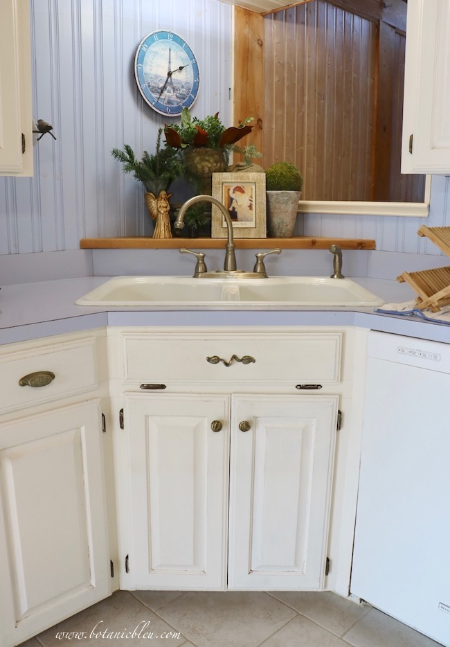 A raised wooden corner shelf behind a corner sink is visible throughout the kitchen and arrangements are not in the way of everyday chores of preparing food and washing dishes