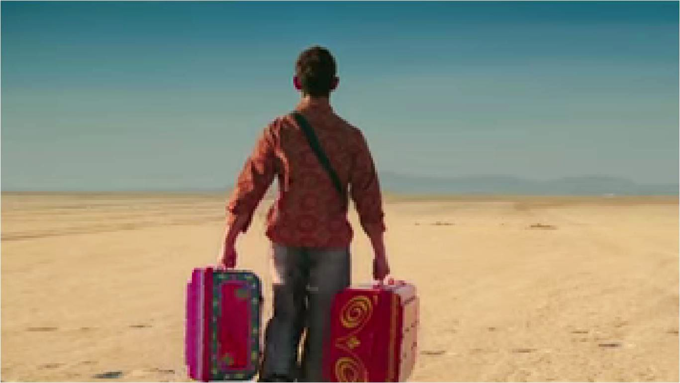Aamir Khan walking in Rajasthan's desert area with two big colorful suitcases in PK movie still