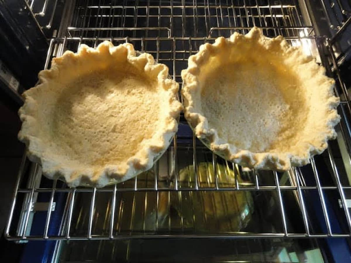 Baked Flaky Pie Crust Shells in the oven on a oven rack.
