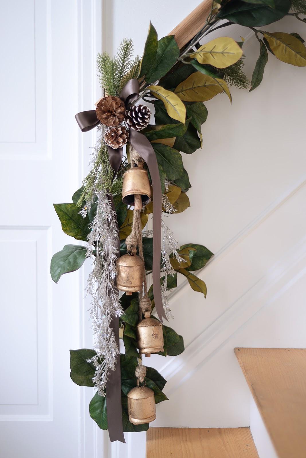 magnolia garland on stair handrail, brass bells, brown satin ribbon