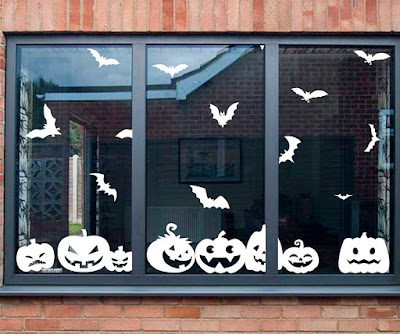 A window with white halloween window stickers in the shape of bats and pumpkins