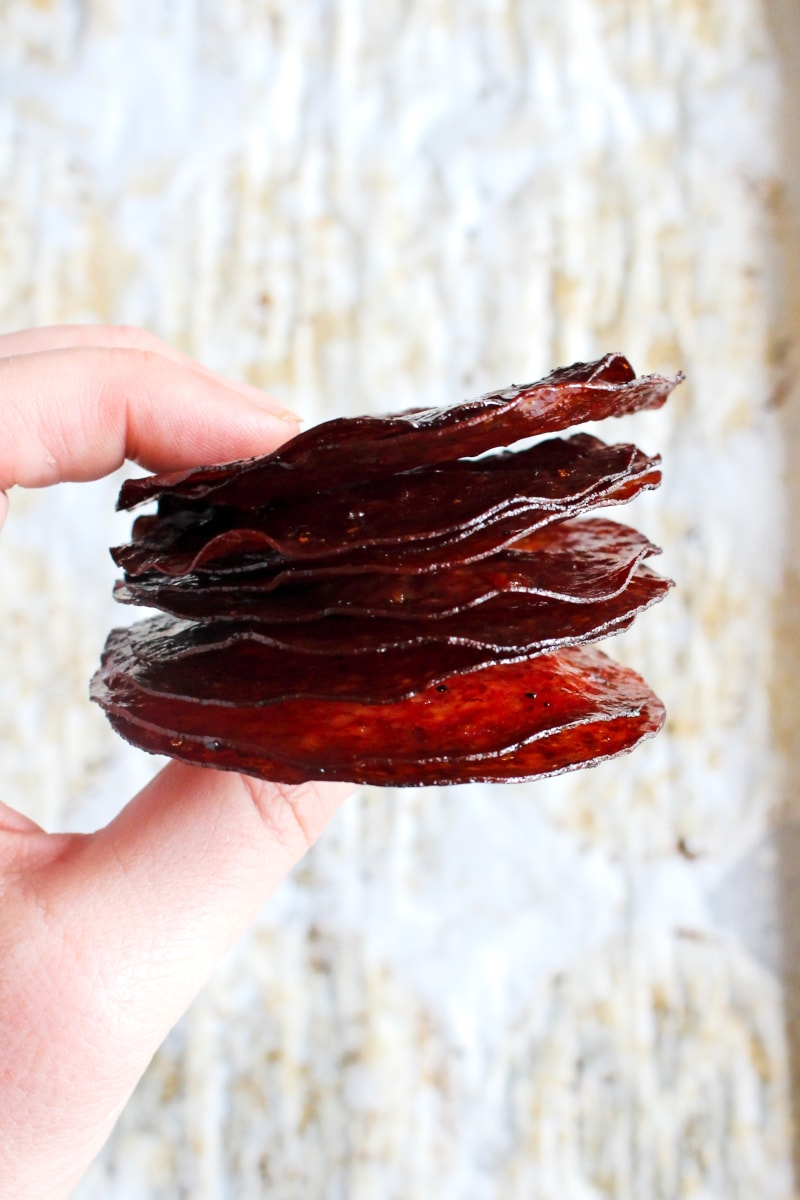 A hand holding a stack of salami chips with a white background.
