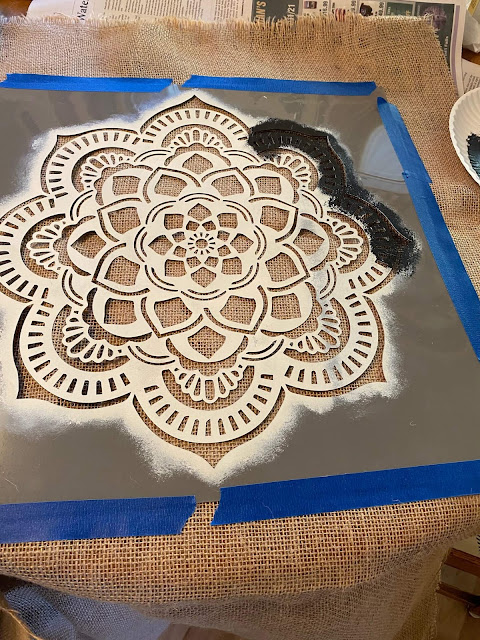 Photo of mandala stencil taped to burlap fabric