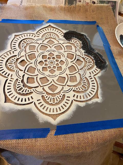 Photo of mandala stencil taped to burlap fabric