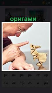 мужчина сделал оригами небольшое животное