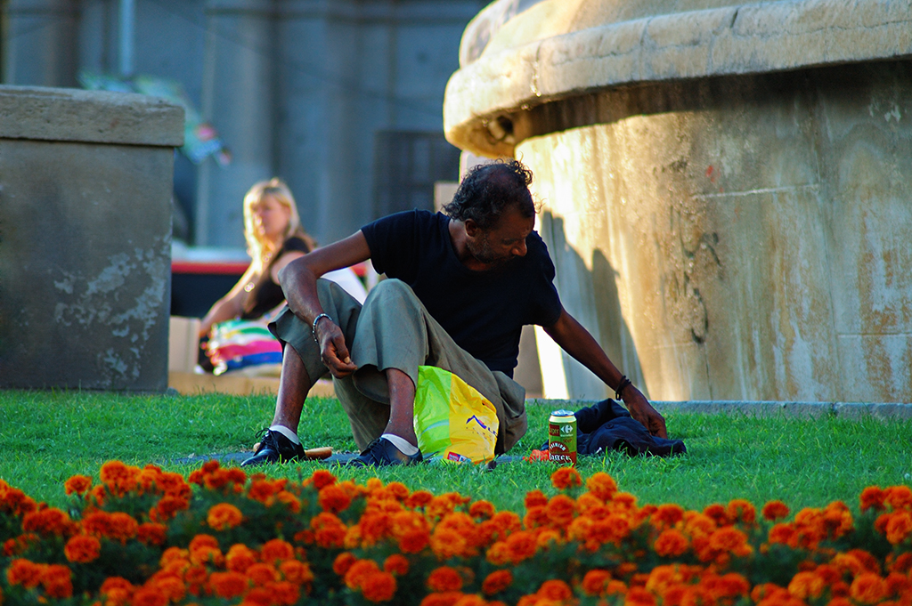Man sitting on grass in Catalonia square or Plaza Catalunya, Barcelona