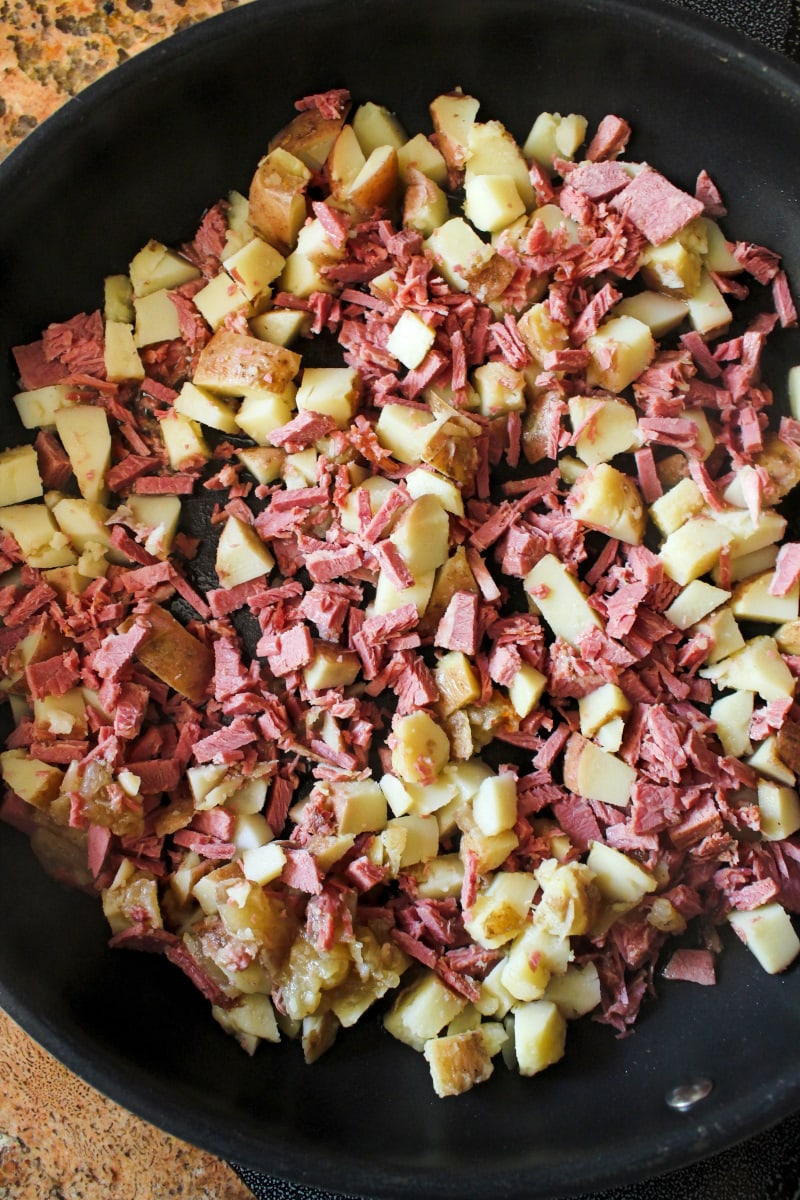 Top view of corned beef and potatoes in a frying pan.