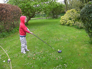 boy playing with full sized golf driver in the garden