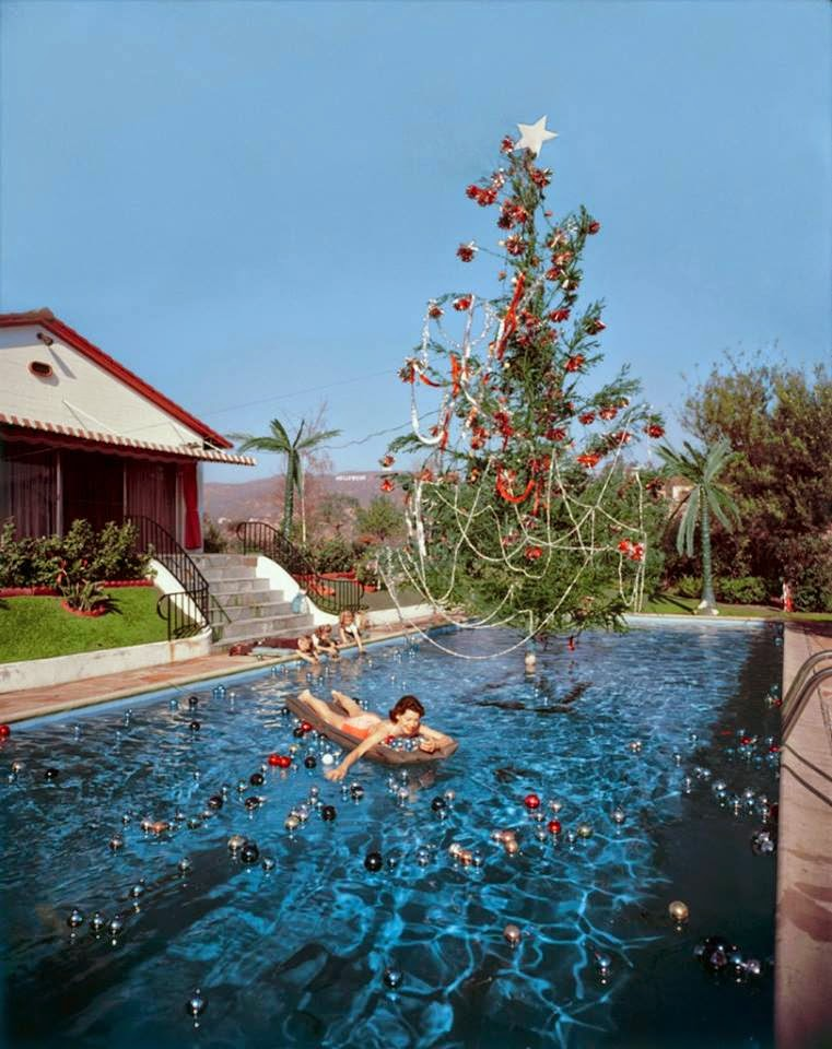 Rita Aarons, wife of the photographer, swimming in a pool festooned with floating baubles and a decorated Christmas tree in Hollywood, 1955. Photo by Slim Aarons